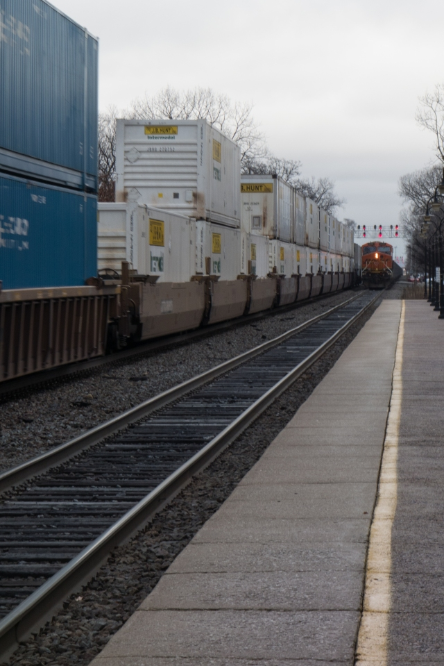 "A container ""Z"" train heads west while a trailing unit pushes an empty coal train into Chicago."