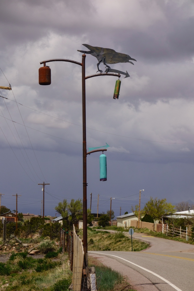 Crow on an art gallery sign on the high road to Taos, New Mexico