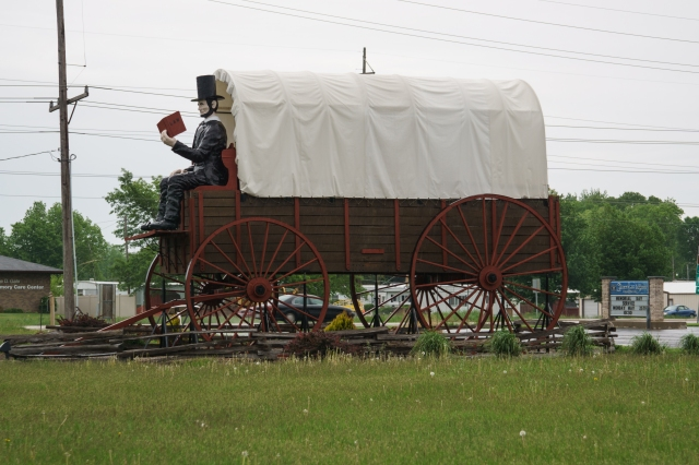 Giant Lincoln reading a book and riding in a covered wagon in Lincoln, Illinois