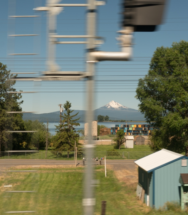 Train signal, telephone wires, farmland, lake, and mountain